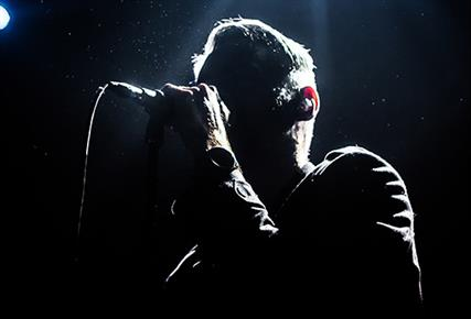 silhouette of man singing on stage