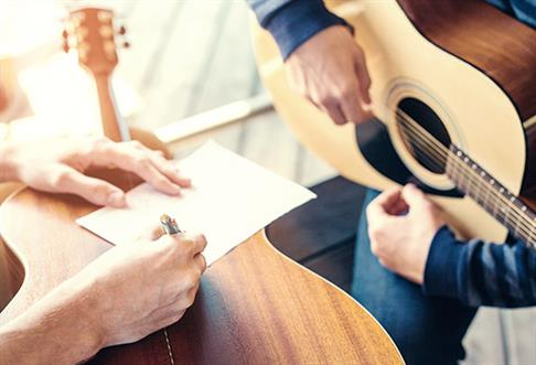 two people writing music and playing guitar